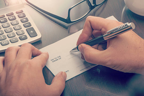 Man writing a payment cheque stock photo