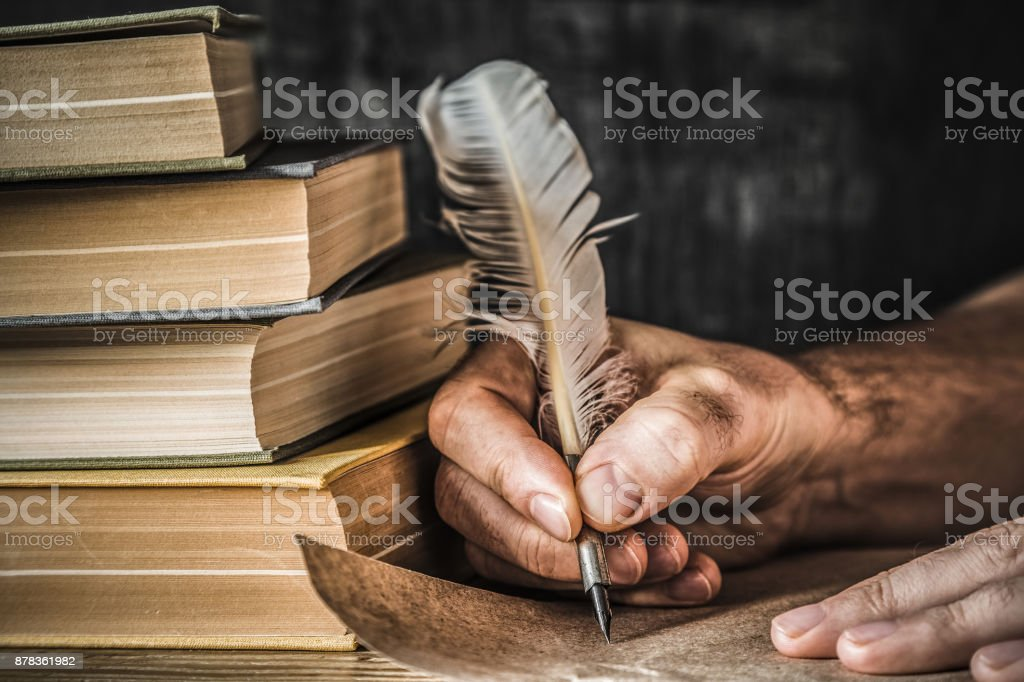 Man writing an old letter. Old quill pen, books and papyrus scroll on the table. Historical atmosphere. stock photo