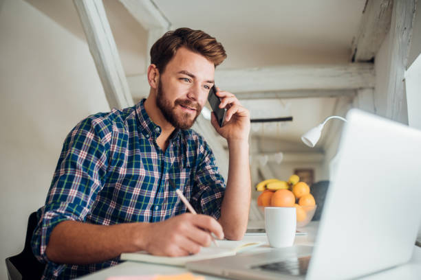Man writing and talking on phone Happy young man using modern technology and writing at the same time applicant stock pictures, royalty-free photos & images