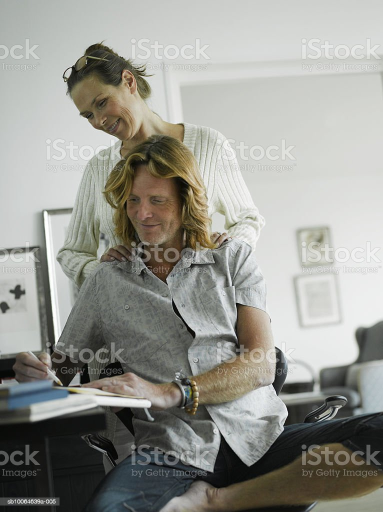 Man writing at table, woman standing behind royalty-free stock photo