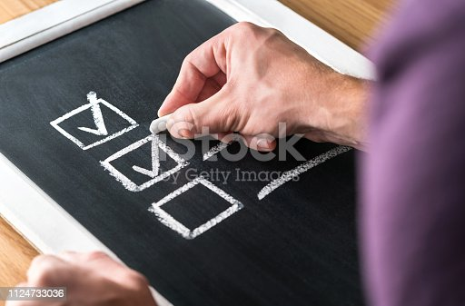 istock Man writing checkmark to checklist on blackboard. Document of finished work and completed tasks on chalkboard. Check list for planning and keeping score. Project management and leadership. 1124733036