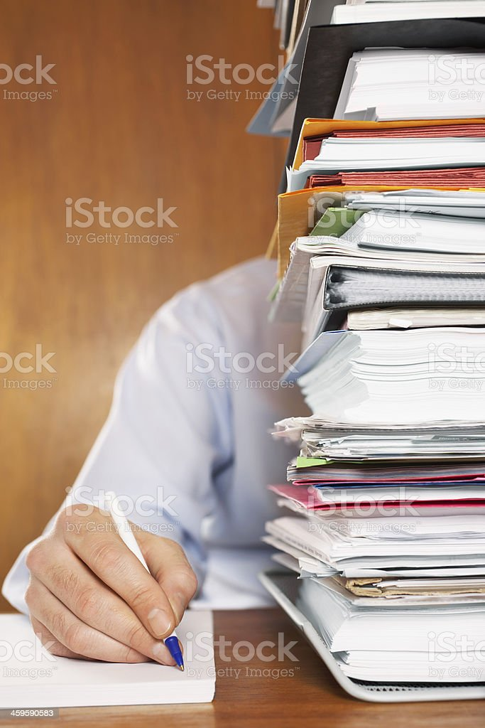 Man Writing Document Behind A Stack Of Folders stock photo