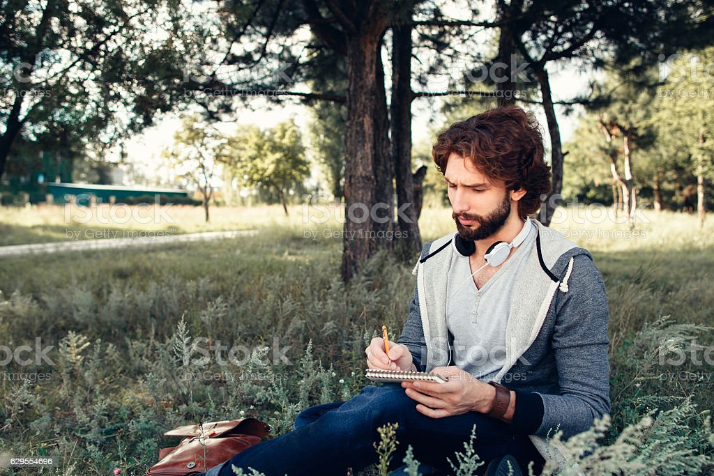 Man writing in copybook at nature, free space stock photo