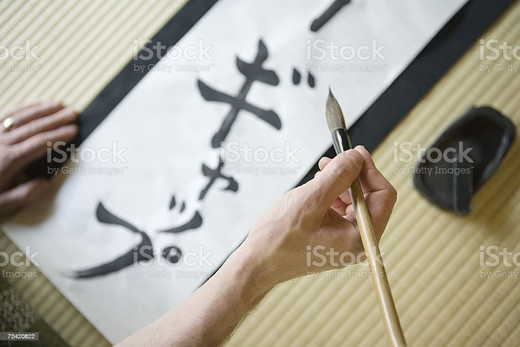 Man writing in Japanese script stock photo