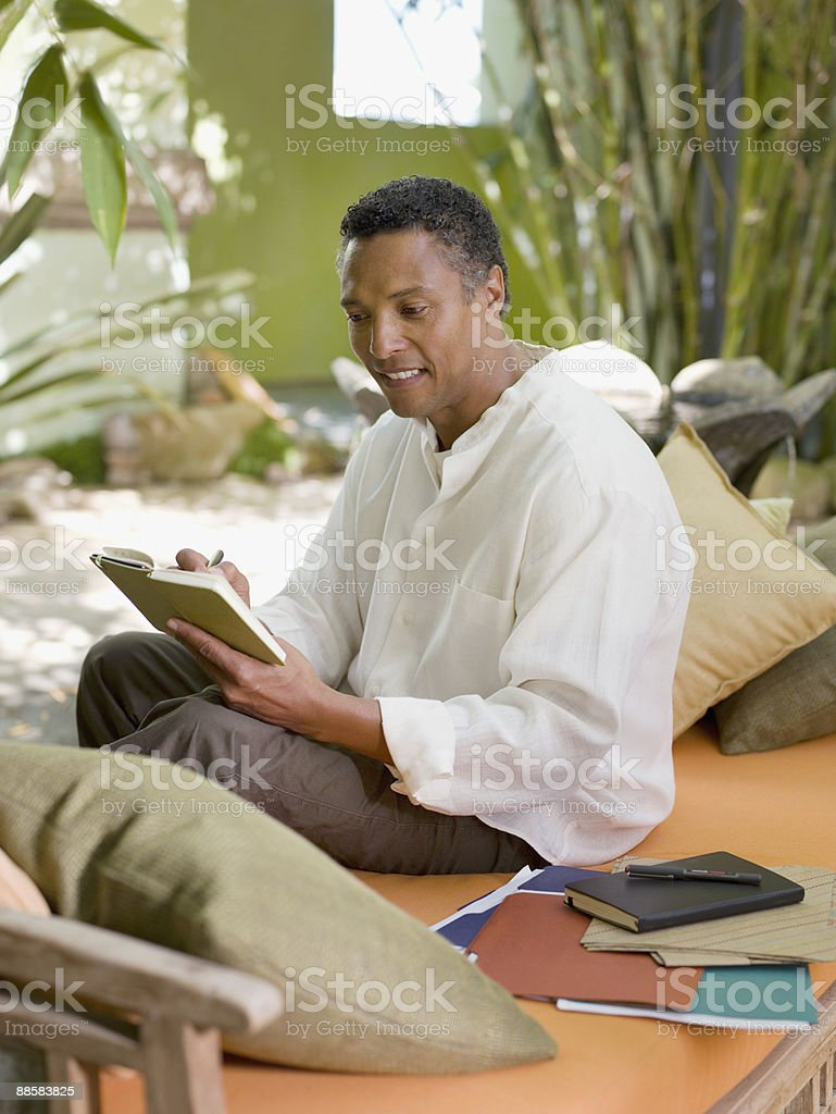 Man writing in journal on patio royalty-free stock photo