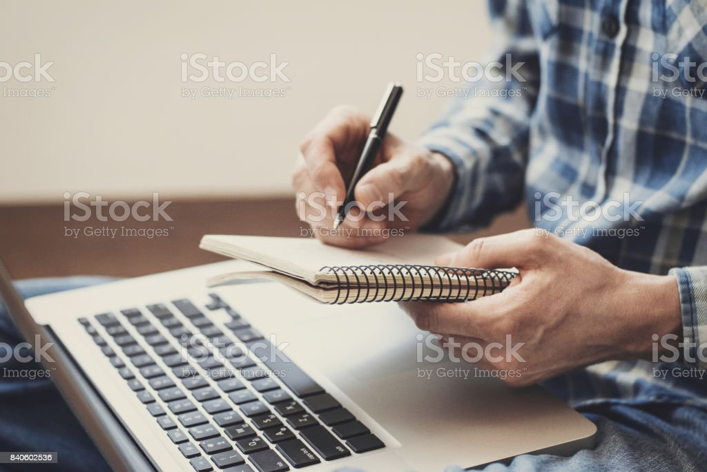 Man writing in notebook Close-up of male hands is writing in his notebook. Journalist blogger writing an article Adult Stock Photo