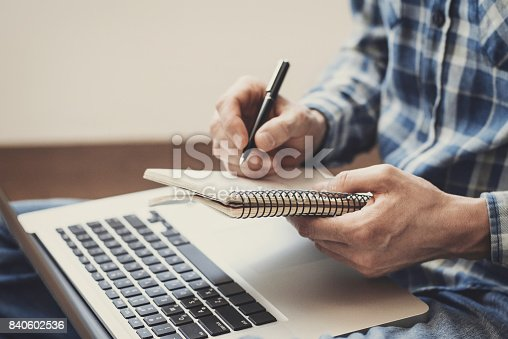 istock Man writing in notebook 840602536