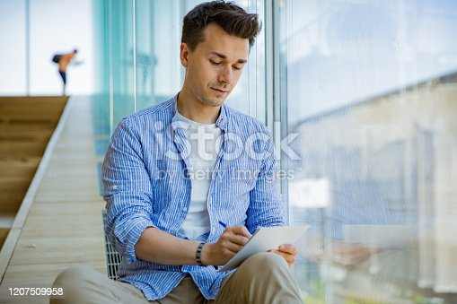 926239360 istock photo Man writing in notebook, sitting on steps at big windows, big working space. 1207509958
