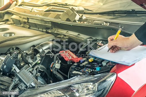 istock Man writing note on book, paper or notepad with blurred engine background.For automotive, transportation maintenance image. 935138682