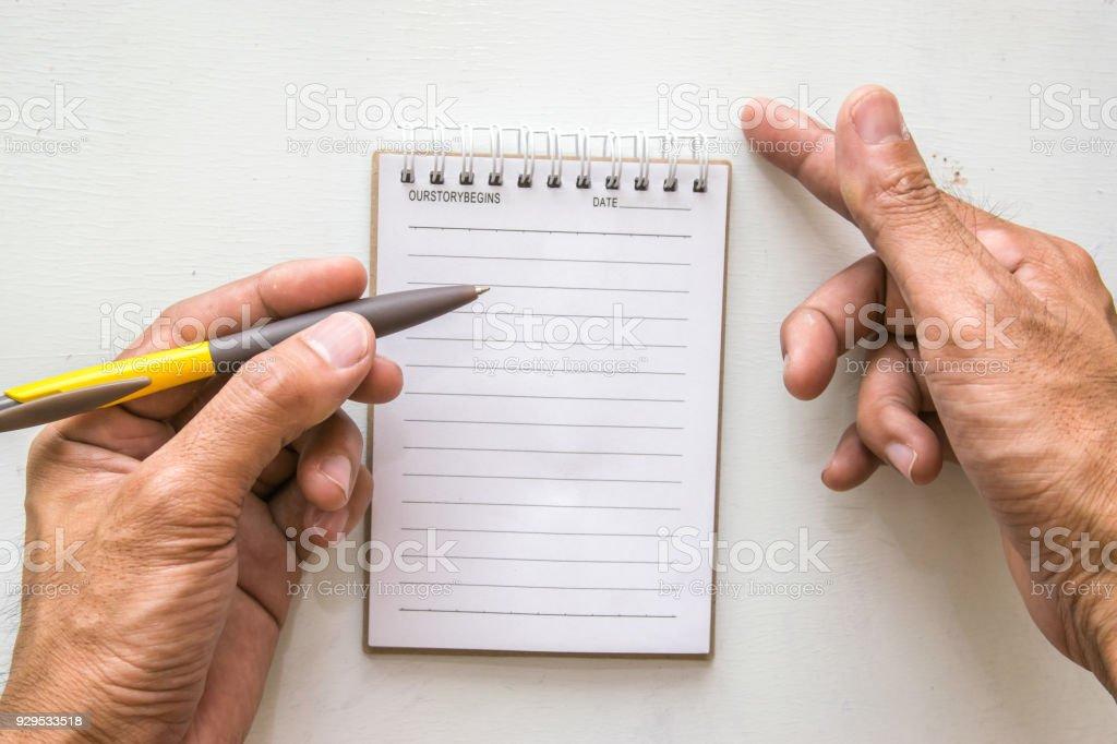Homme qui rédige les blocnotes et un crayon sur papier peint de