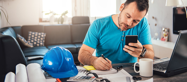 Man in blue shirt writing notes and holding smart phone at home office