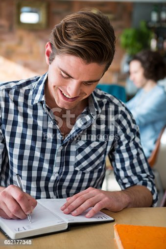 istock Man writing notes in diary in coffee shop 652177348