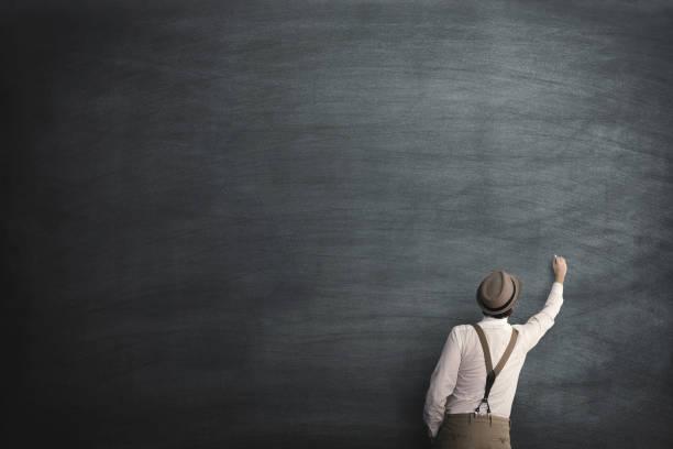 man writing on an empty chalkboard stock photo