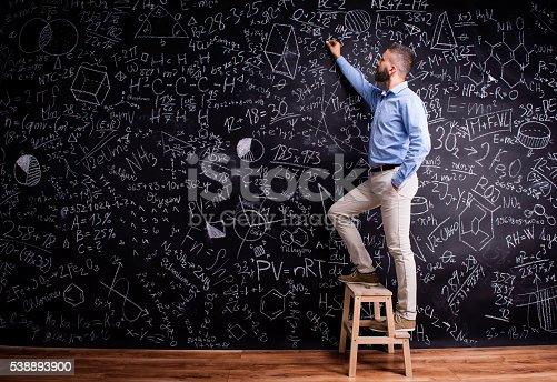 istock Man writing on big blackboard with mathematical symbols 538893900