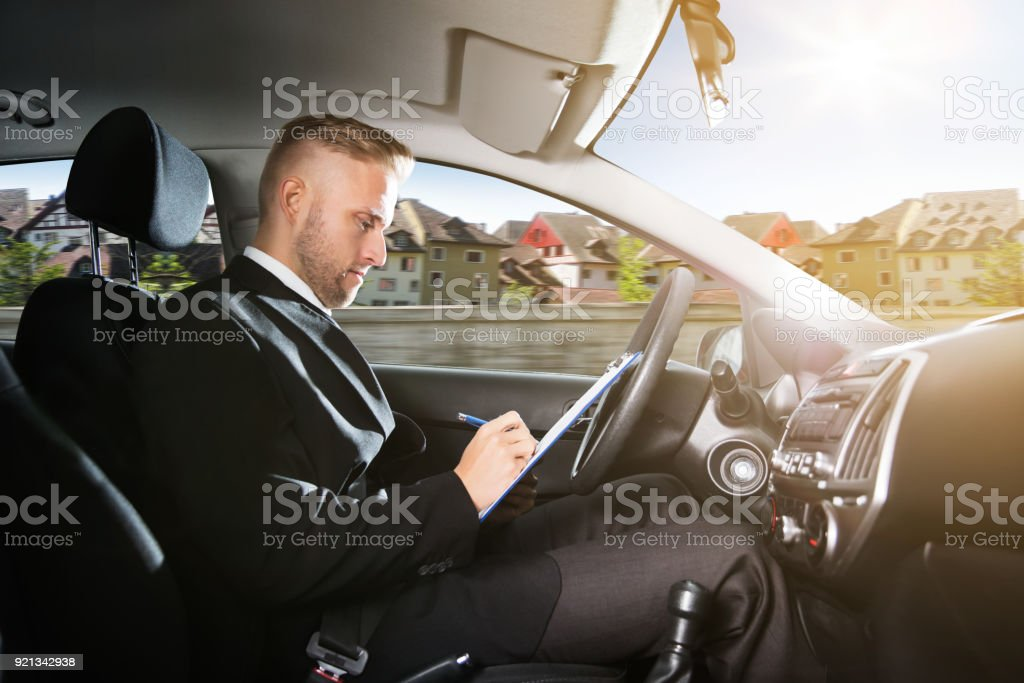 Side View Of A Man Writing On Clipboard Inside Self Driving Car