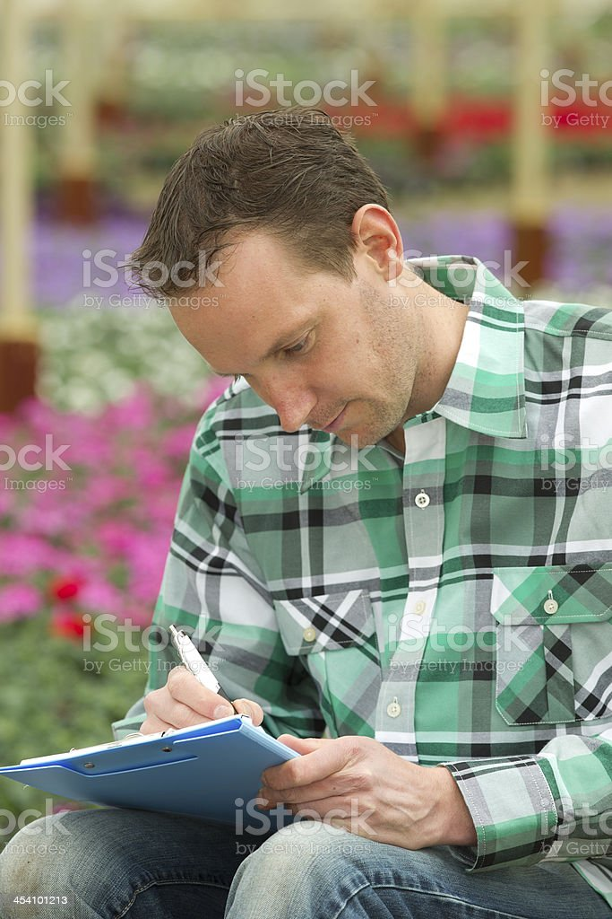 Man Writing On Clipboard While Sitting In Greenhouse royalty-free stock photo