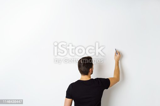 istock Man writing on white wall 1146435447
