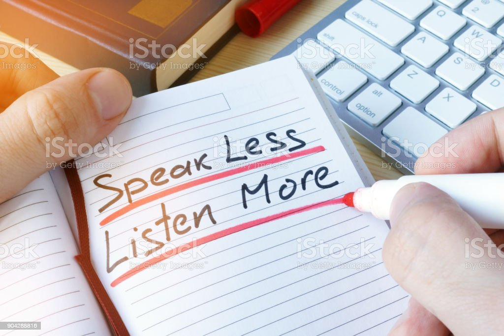 Man writing quote Speak less listen more. stock photo