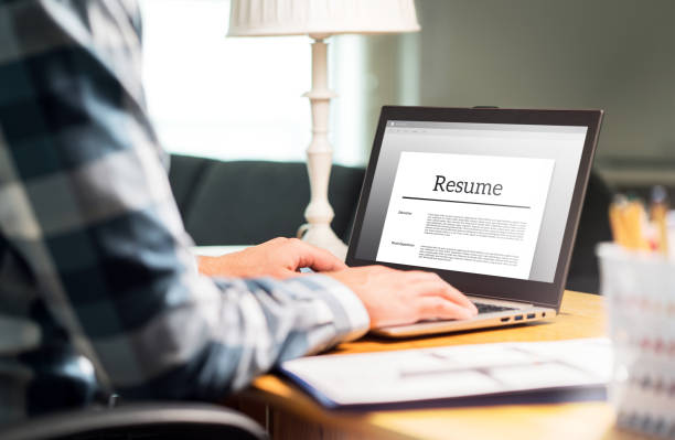 Man writing resume and CV in home office with laptop. Applicant searching for new work and typing curriculum vitae for application. Job seeking, hunt and unemployment. stock photo