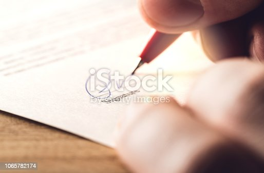 istock Man writing signature with pen on paper. Settlement for acquisition, business deal, bank loan or rental apartment. Signing contract, agreement, car lease or legal document. 1065782174