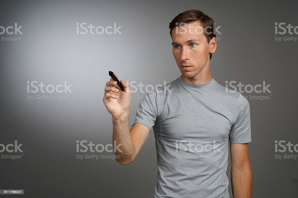 Man writing something with marker on glass board. stock photo