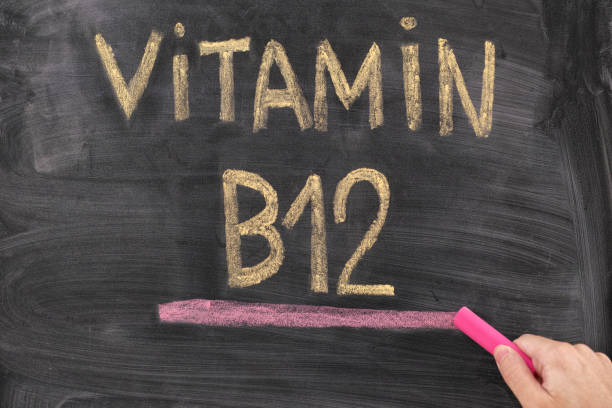 man writing words vitamin b12 on chalkboard - deficient stock pictures, royalty-free photos & images