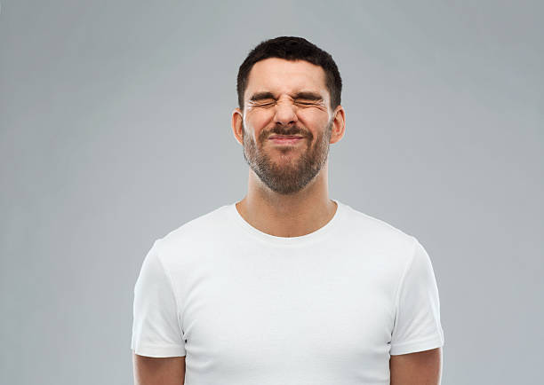 man wrying over gray background emotion and people concept - young wrying man over gray background grimacing stock pictures, royalty-free photos & images