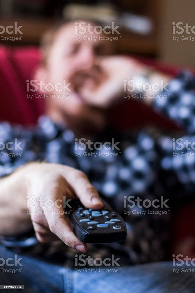 Man yawning while zapping on remote controller stock photo