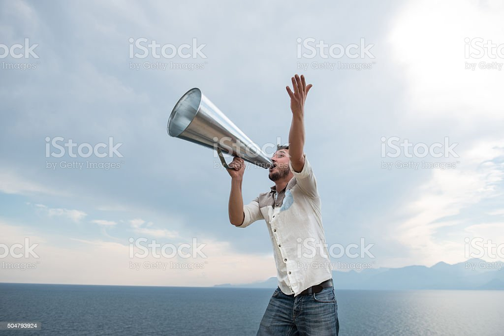 Man yelling trough a megaphone stock photo