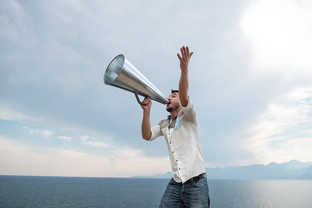 Man yelling trough a megaphone stock photo
