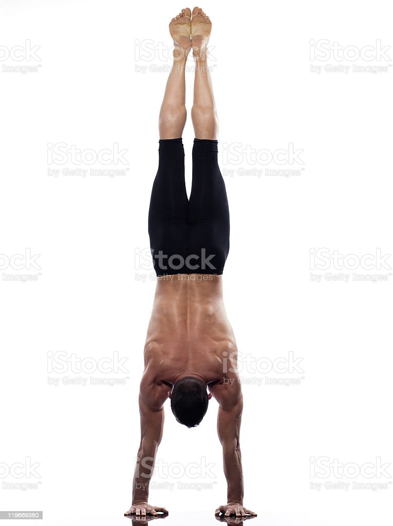 Man yoga handstand Adho Mukha Vrksasana pose stock photo