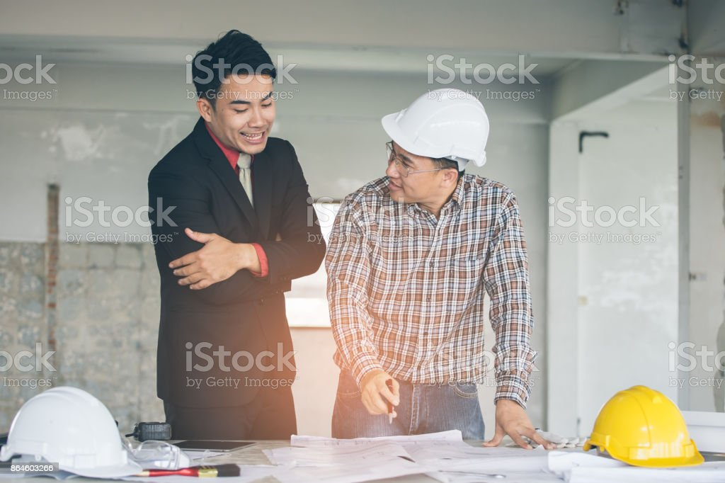 Management consulting with engineers working with blueprint and management consulting with engineers working with blueprint and drawing on work table royalty free malvernweather Choice Image