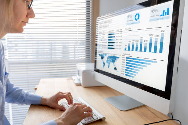 Manager analysing performance data on dashboard with KPI and metrics. Business analytics used in operations and sale management. Businesswoman working in modern office with indicators. stock photo