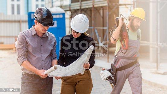 istock Manager and architect examining blueprints 624154712