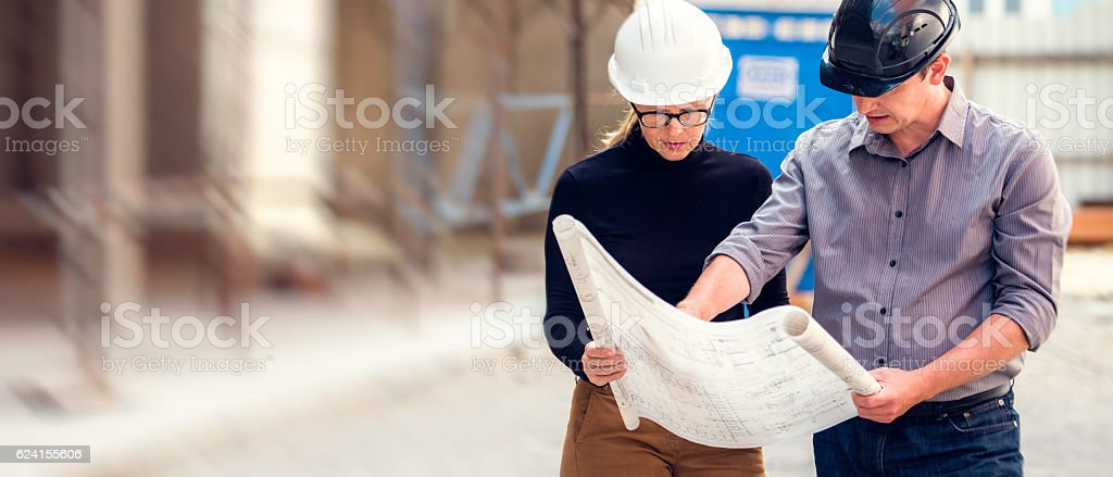 Manager and architect reviewing blueprints at a construction site stock photo