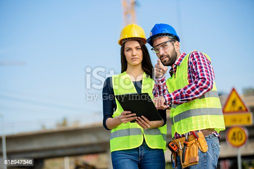 617878058 istock photo Manager and construction worker cheking papers 618947346