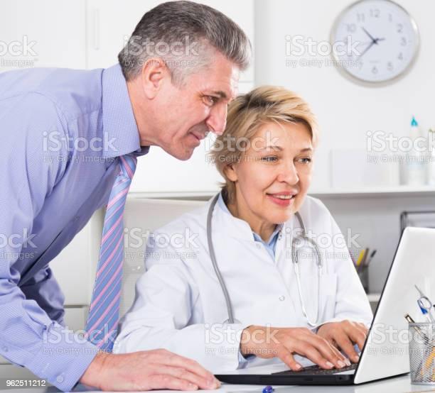 Foto de Gerente E Médico Ler Notícias e mais fotos de stock de Adulto