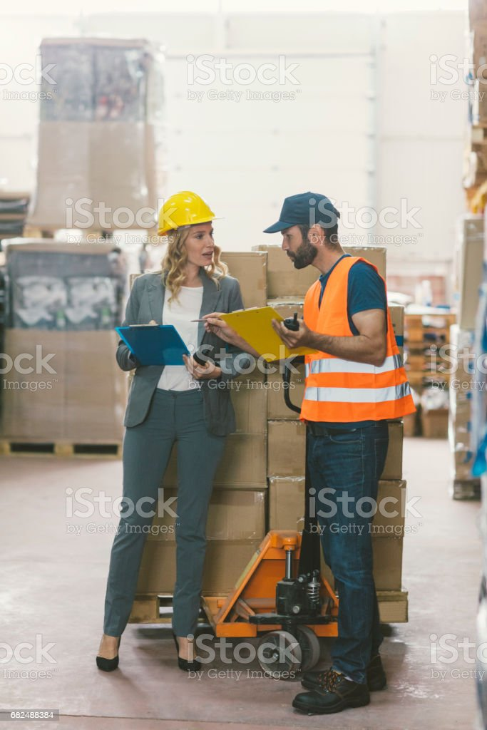 Manager and manual worker in warehouse Стоковые фото Стоковая фотография