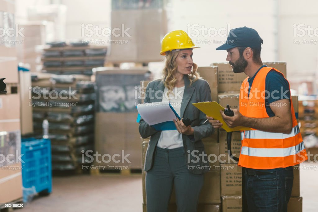 Manager and manual worker in warehouse royalty-free stock photo