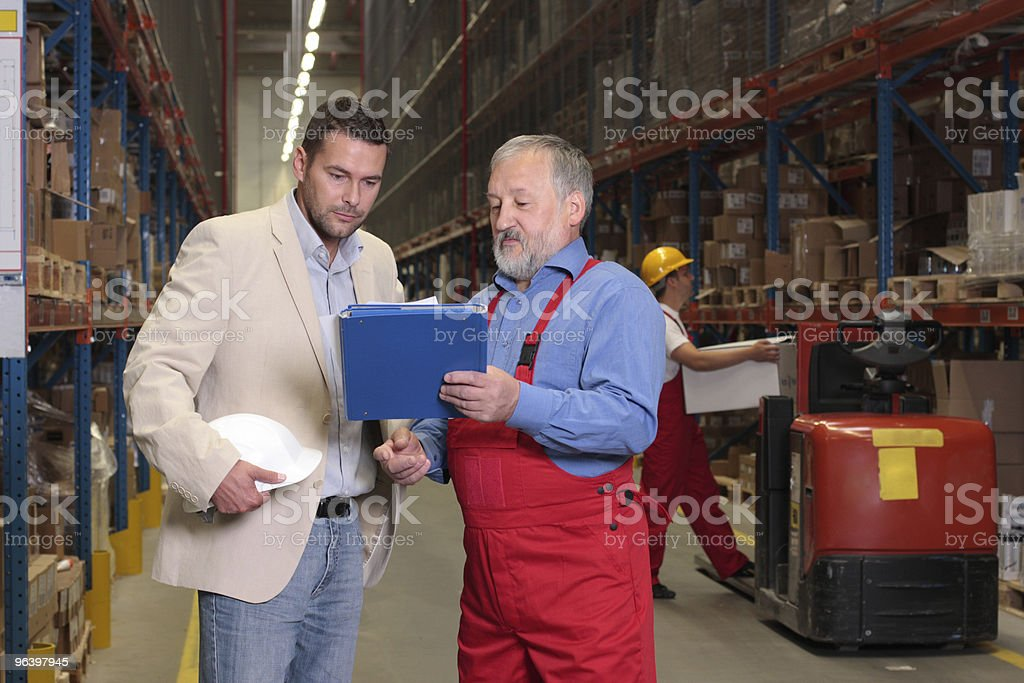 manager and older worker browsing  papers in warehouse royalty-free stock photo