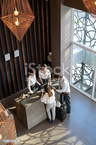 istock Manager and receptionist at a hotel checking in a business couple while both are looking at their smartphones 1068158538