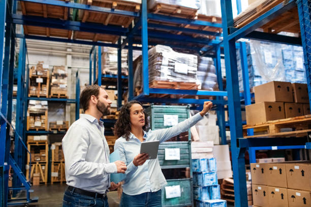 Manager and supervisor taking inventory in warehouse Businesswoman with a digital tablet showing and talking with male worker in distribution warehouse. Manager working with foreman in warehouse checking stock levels. manufacturing stock pictures, royalty-free photos & images