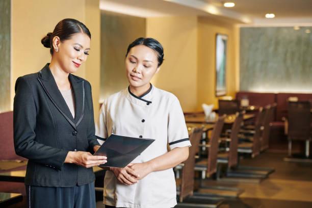 Manager und Kellnerin beim Lesen eines Menüs – Foto