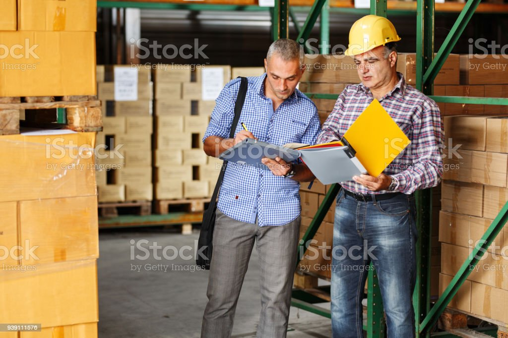 Manager and warehouse worker checking list and inventory on the shelf in storehouse. stock photo