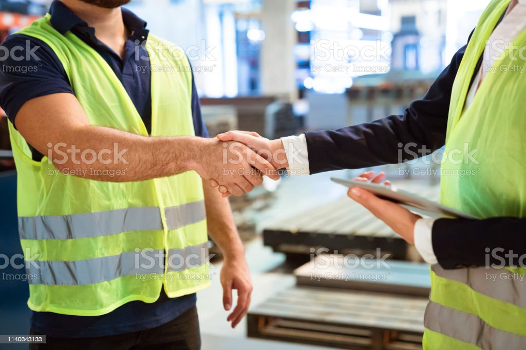 Manager and worker greeting each other in factory Midsection of manager shaking hand with production worker in factory. Engineers are wearing reflective clothing. They are greeting each other. 20-24 Years Stock Photo