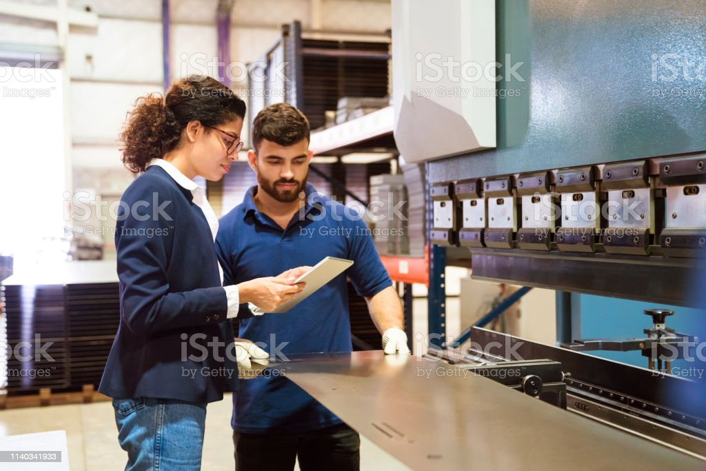 Manager and worker working in factory Manager showing digital tablet to production worker. Male engineer is manufacturing sheet metal. Female inspector is on visit in factory. 20-24 Years Stock Photo