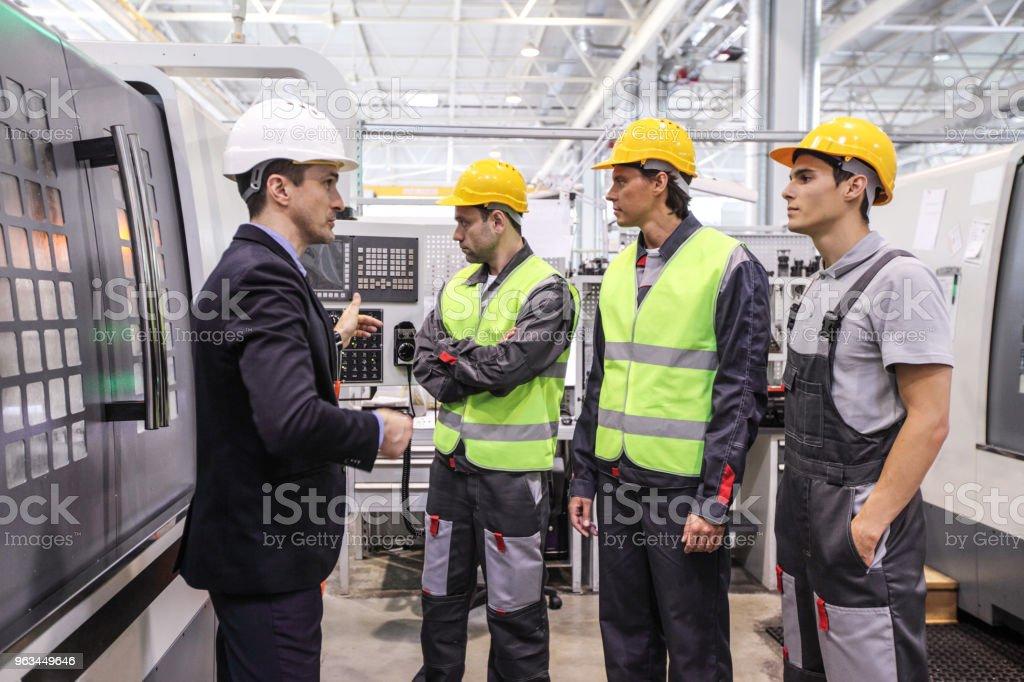 Kierownik i pracownicy w pobliżu maszyn CNC - Zbiór zdjęć royalty-free (Inżynier)