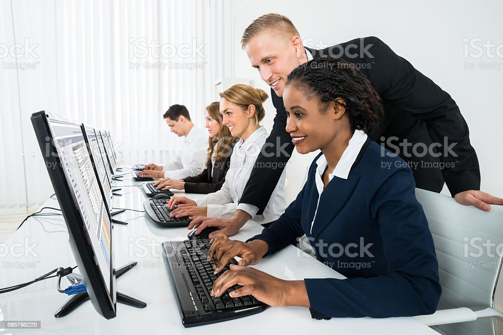 Manager Assisting His Staff In Office stock photo
