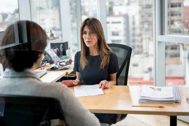 personalleiterin in ihrem büro im fröhlichen gespräch mit der mitarbeiterin - leitende position stock-fotos und bilder