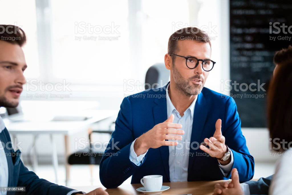 Manager discussing with colleagues during meeting Confident male manager discussing with colleagues during meeting. Design professionals are planning strategy at workplace. They are sitting at creative office. 30-39 Years Stock Photo